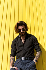 Man posing in yellow wall