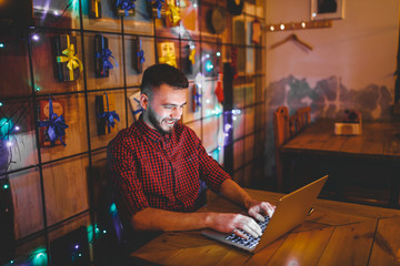 Theme training and computers. A young man with a beard and in a shirt uses a laptop, prints on the keyboard in a coffee shop at a wooden table in the evening. Christmas decor and hang a garland