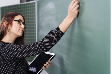 Young woman holding tablet writing on blackboard