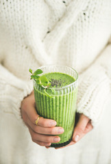 Matcha green vegan smoothie with chia seeds and mint in glass in hands of female wearing white sweater. Clean eating, detox, alkaline diet, weight loss concept