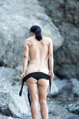 Brunette woman undressing on rocky seashore in cloudy day