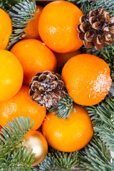 Christmas composition with tangerines, gift boxes, cones on a dark wooden background. Top view with copy space.