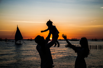 Happy family - silhouette of father tossing baby girl and mother on sunset sea