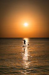 Silhouette of man standing up at paddle Board on sunset, Boracay. Philippines.
