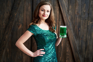 Sexy smiling woman holding mug of green beer for St. Patricks Day celebrations on wooden background, copy space. Girl in emerald sequins dress holding glass of beer in pub. Greeting card, March 17