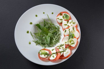 tomato salad with mozzarella cheese and sauce in white plate on black background, isolated