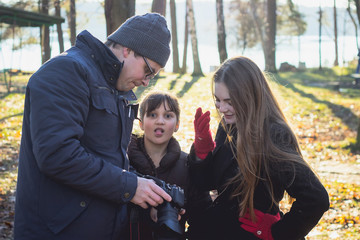 a man shows to girls photo in the woods