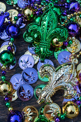 mardi gras necklaces and beads with green, gold, and purple fleur de le coins