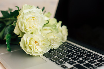 Bouquet of white roses lying on laptop. Top view