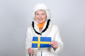 Senior woman holding a flag of Sweden. Adult woman is 70 years of age. Pensioner. Old female is dressed in warm winter clothes standing on a light background.