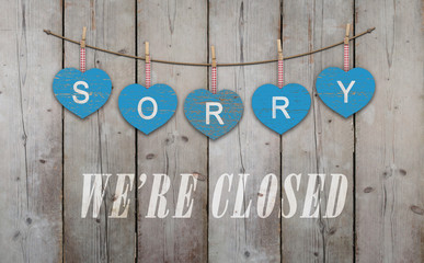 blue wooden hearts with text sorry we are closed, on old scaffolding wooden backdrop, with copy space