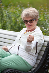 Aggressive elderly woman is threatened with a fist while sitting on park bench