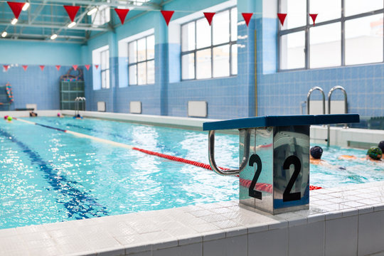 Starting platform with number two is in a swimming pool for children groups. Kids practice with instructor