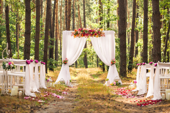 Beautiful romantic festive place made with wooden square and floral roses decorations for outside wedding ceremony in green park. Wedding settings at scenic place. Horizontal color photography.