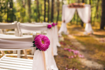 Closeup view of beautiful floral elements of wedding decorations. Settings for romantic wedding ceremony outside at sunny forest. Horizontal color photography.