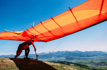 Zelfklevend Fotobehang Luchtsport Man with hang-glider starting to fly from the hill top