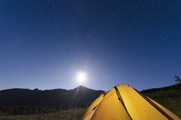 tourist tent in the mountains under the moonlight