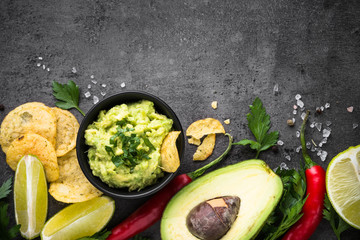 Traditional latinamerican mexican sauce guacamole on black.