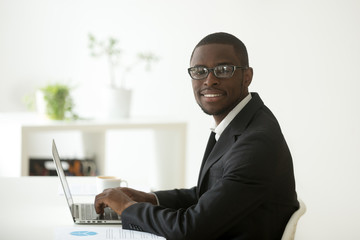 African-american smiling businessman in suit and glasses working on laptop, friendly black financial accountant, marketing manager, business analyst or ceo looking at camera at workplace, portrait