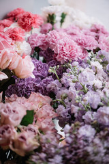 Beautiful freshly delivered to a florist shop flowers in pastel pink colors, looks like endless flower texture, vertical photo