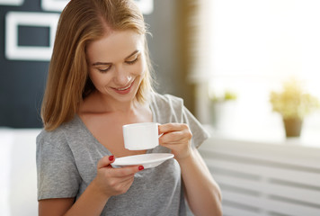 happy young woman with cup of morning coffee in bed