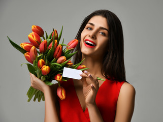Beautiful woman with bouquet of tulip flowers in red dress and little sticker on tulips with free empty text space