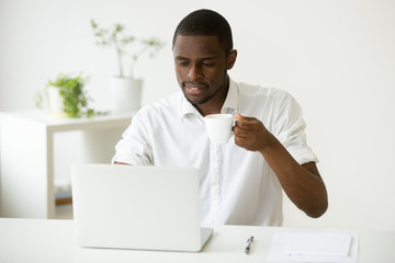 Smiling attractive african american man enjoying coffee while using laptop sitting at home office desk, black businessman checking online news or computer emails relaxing having morning break at work