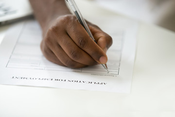 African american man filling employment application, black jobless person applicant writing personal information in form apply for new job, unemployment and work search concept, close up view of hand