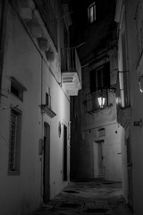 Vertical View in Greyscale of a Street Illuminated By Artificial Light at Night. Martina Franca, South of Italy