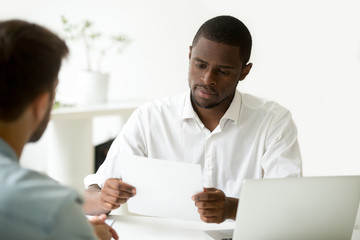Serious african businessman reading document at meeting, black entrepreneur considering contract, company ceo analyzing report, hr manager or employer holding applicants cv resume at job interview