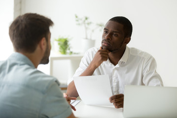 Serious attentive african hr manager listening to caucasian candidate at job interview, focused strict employer thinking having doubt about hiring decision while talking to male applicant in office