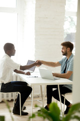 Multiracial handshake, african and caucasian partners shaking hands in office starting successful teamwork promising help and support, diverse entrepreneurs making deal at office desk, vertical view