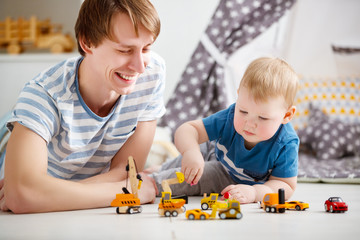 happy family father and son playing in toy car in playroom