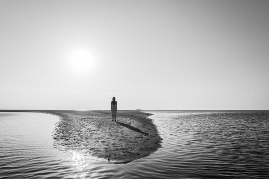 Silhouette of young woman standing alone on small sand island contemplating the sunset in Koh Phangan, Thailand. Black and white photography. Meditation, contemplation, loneliness concept