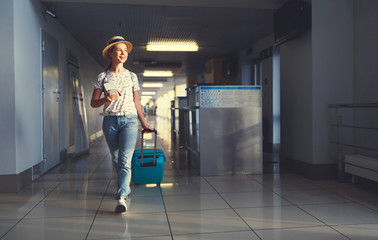 young woman goes  at airport at window with suitcase waiting for plane.