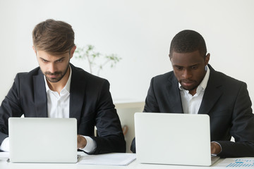Focused busy diverse businessmen working independently on laptops online share office desk, serious african american and caucasian executive team colleagues in suits using two computers at workplace