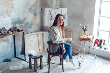 Young woman artist painting at home creative turning back