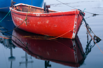 Bright Red Fishing Dory Moored to Blue Boat