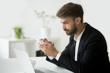 Successful serious businessman using smartphone app for business sitting at workplace with laptop, focused executive in suit texting message or browsing web on corporate mobile phone, gadget for work