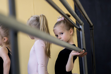 Cute little ballerina looking at the camera. Pretty girl waiting in line for her ballet class.