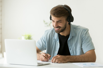 Smiling man in headphones looking at computer screen watching webinar, making business video call, young businessman consulting remote client online writing notes, hr holding distance job interview