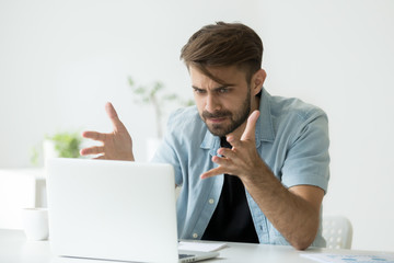 Frustrated angry entrepreneur outraged by laptop problem, furious mad man using computer looking at screen raging after pc software crash error, annoyed guy frustrated disagree with fake online news
