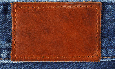 Blank brown leather label on blue jeans background
