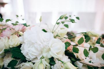 Wedding reception white table arrangement, floral centerpiece decoration, food. Catering service.