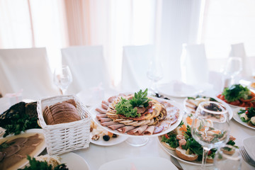 catering table wedding set  with silverware and glass, food and flower decoration
