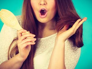 Shocked amazed woman holding hair brush