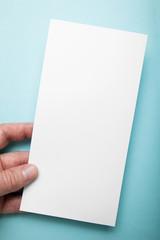 Hand holding vertical blank flyer brochure booklet on blue background. Leaflet presentation.