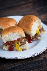 mini hamburger sliders with ketchup, mustard, and pickles on white plate