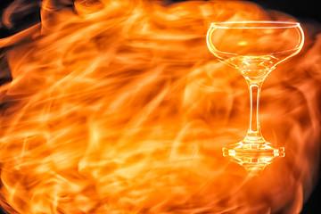 En empty champagne glass in the fire flames.