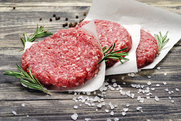 Fresh raw chopped meat for burgers on a wooden table.